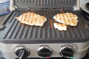 Two chicken breasts grilling on an indoor press.