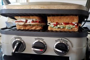 Close up view of two assembled sandwiches grilling in a panini press.