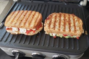 Two grilled sandwiches in a panini press.