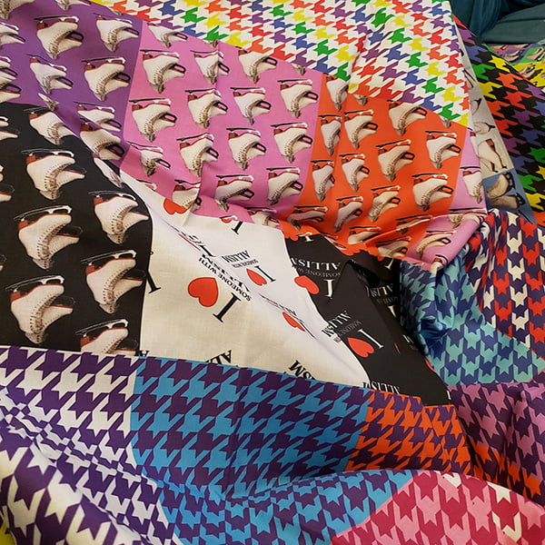 Image features a variety of brightly coloured print fabrics in a pile.