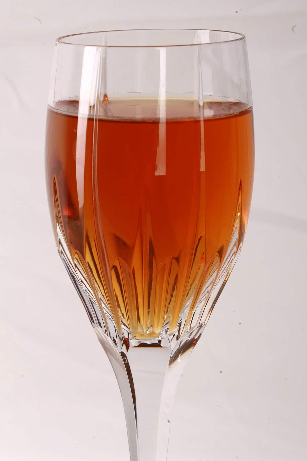 Close up photo of a tall wine glass with dark amber mead in it.