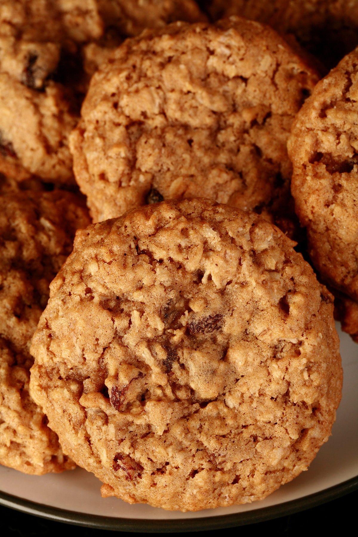 A close up view of a plate of spiced oatmeal raisin cookies.