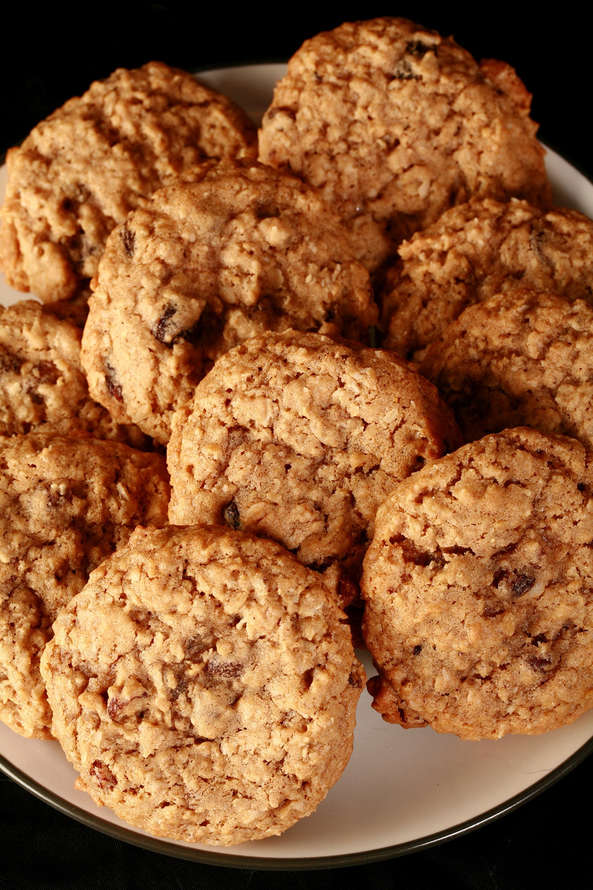 A close up view of a plate of spiced chewy oat raisin cookies.