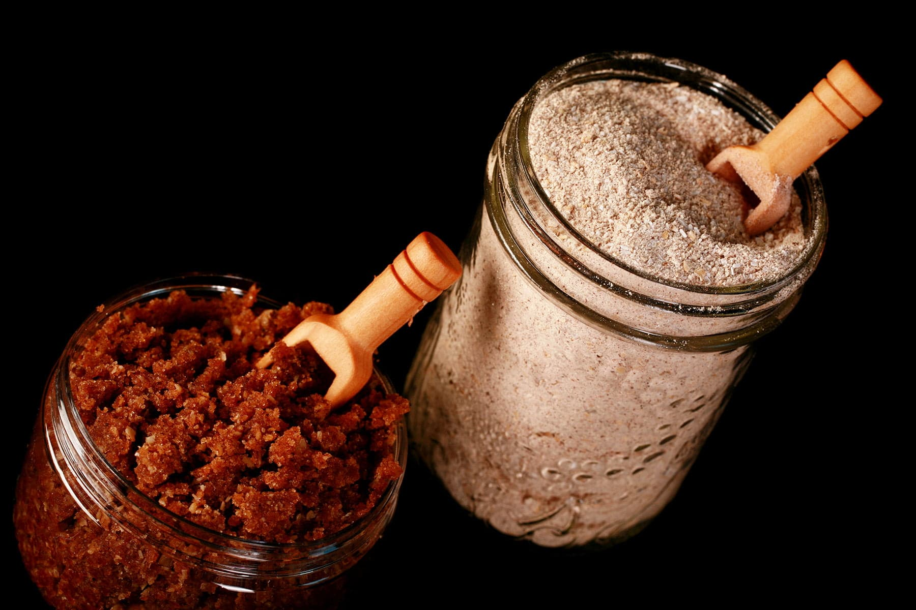 A two piece bath set pictured against a black background. A Mason jar contains an ivory coloured Oatmeal Milk Bath powder, and a smaller jar contains a rich brown Oatmeal Sugar Scrub