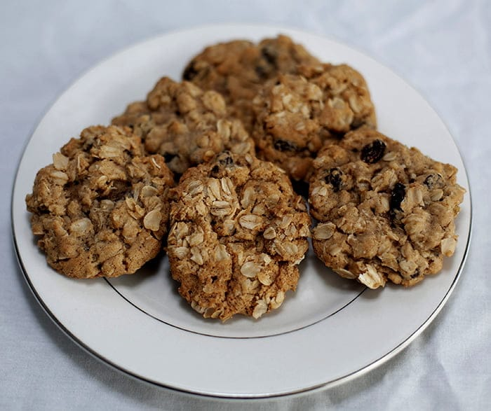 A white plate stacked with oatmeal raisin cookies.