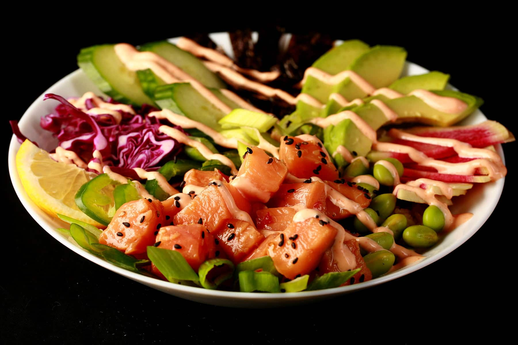 lose up view of a spicy salmon poke bowl - chunks of marinated salmon and veggies, drizzled with a light pink dynamite sauce.