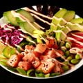 Close up view of a spicy salmon poke bowl - chunks of marinated salmon and veggies, drizzled with a light pink dynamite sauce.