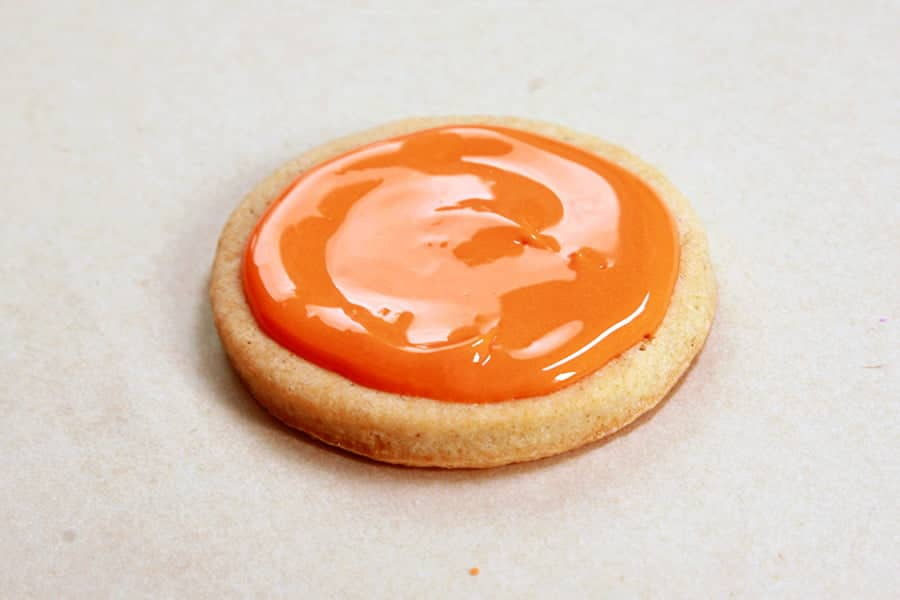 A single round cookie, with orange frosting covering the top.
