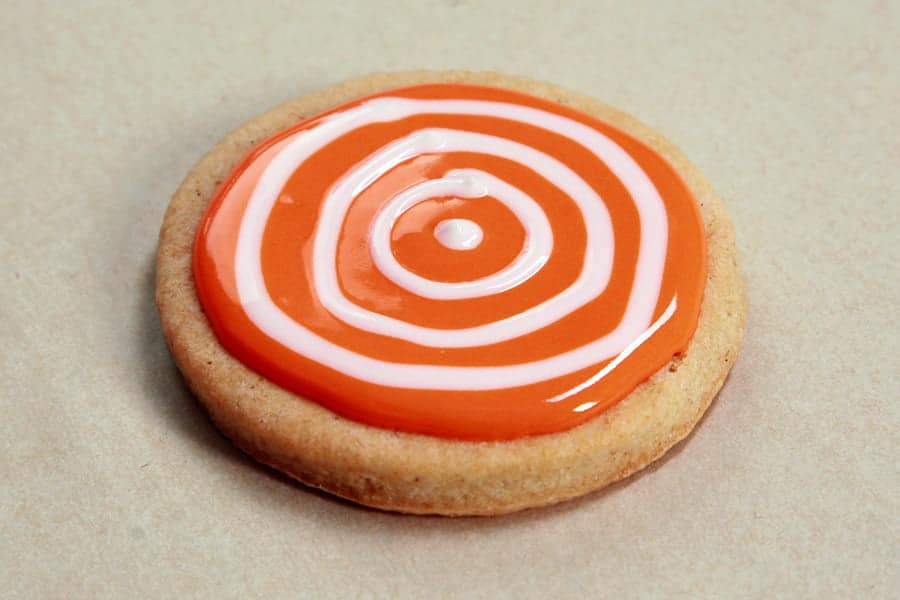 A single round cookie, with orange frosting covering the top. There are concentric circles of white frosting piped over the orange.