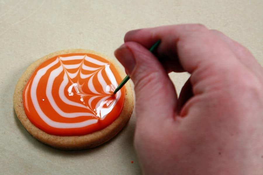 A hand is using a tooth pick to draw the frosting outward from the center of the cookie.