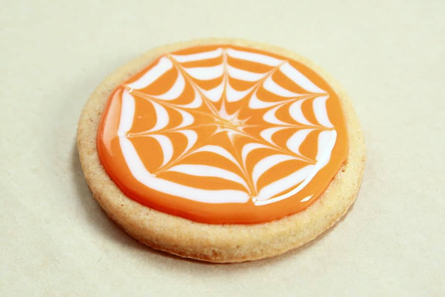 A single cookie with orange and white frosting on top. The white frosting forms a stylized spider web design.