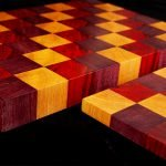 A close up view of 2 DIY cutting boards, each made up of colourful squares of wood - red, purple, and yellow.
