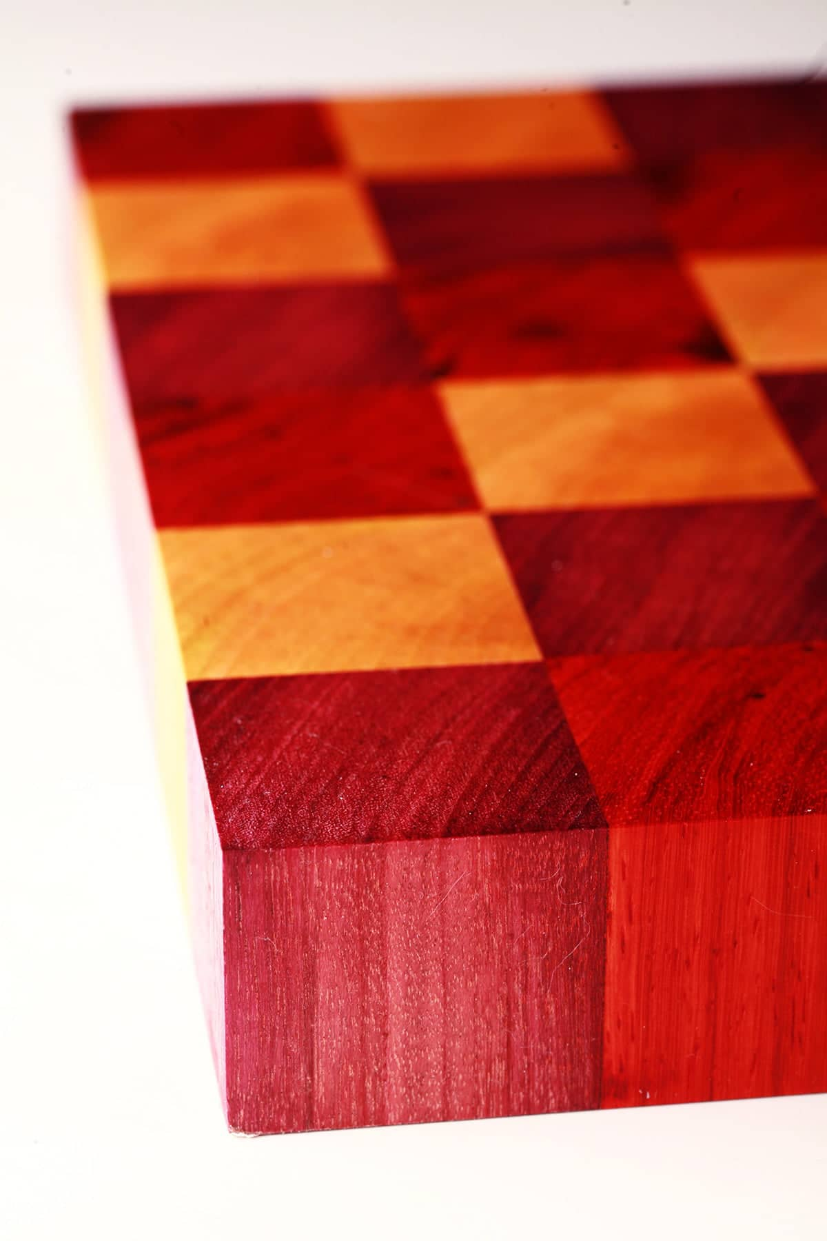 A close up view of a DIY cutting board, made up of colourful squares of wood - red, purple, and yellow.