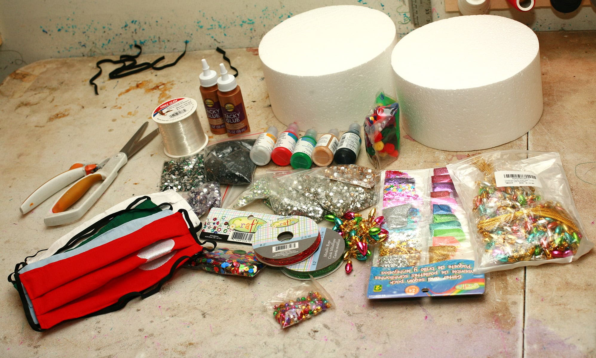 A selection of craft supplies is arranged on a work surface. There are paints, glitters, glues, sequins, beads, and more.