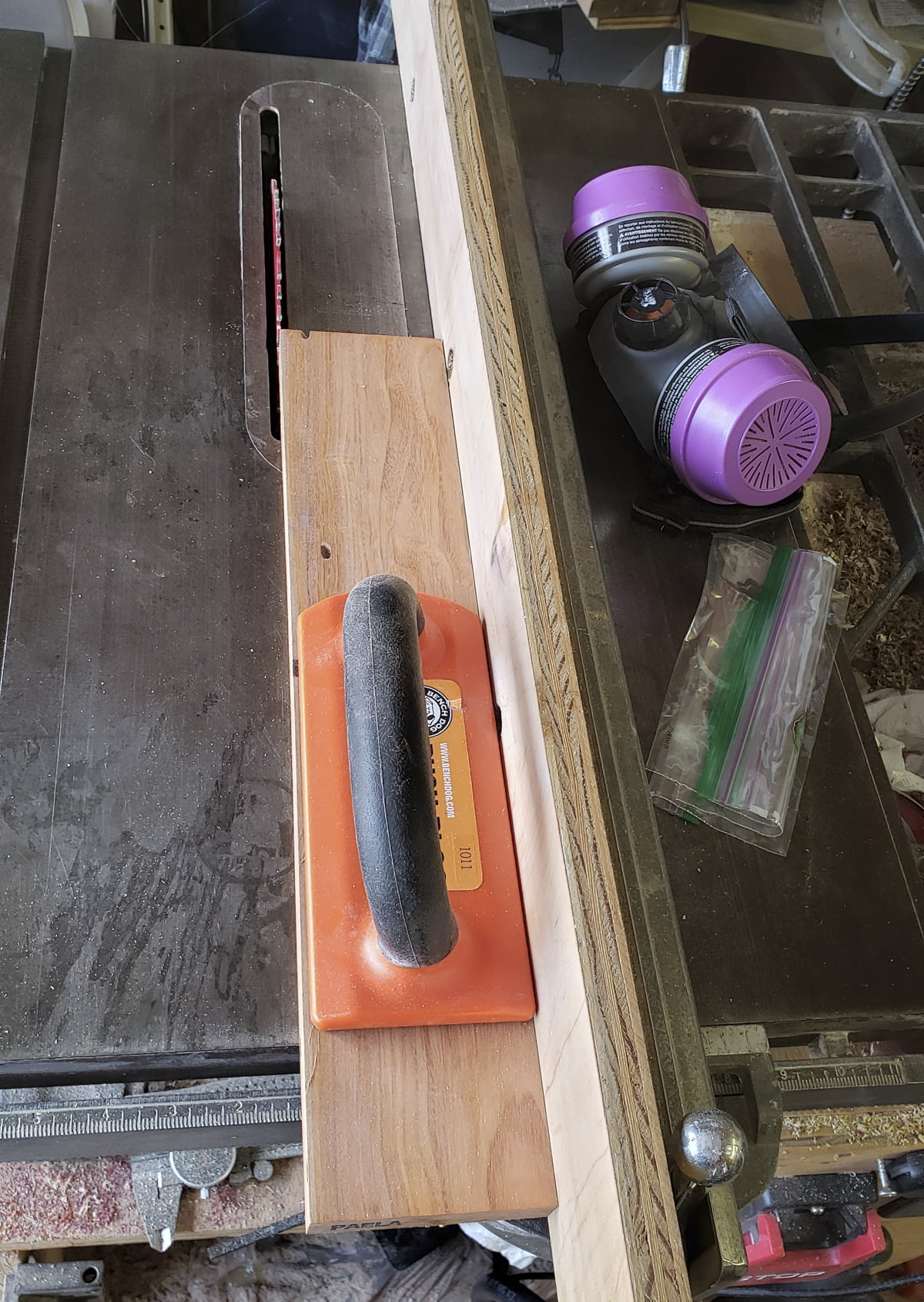The top of a table saw, with a push block on it.