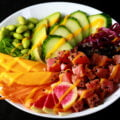 Close up view of a colourful bowl of tuna mango poke. There is a rainbow of vegetables and fruit, including purple cabbage, watermelon radish, carrots, mango, edamame, avocado, and cucumber
