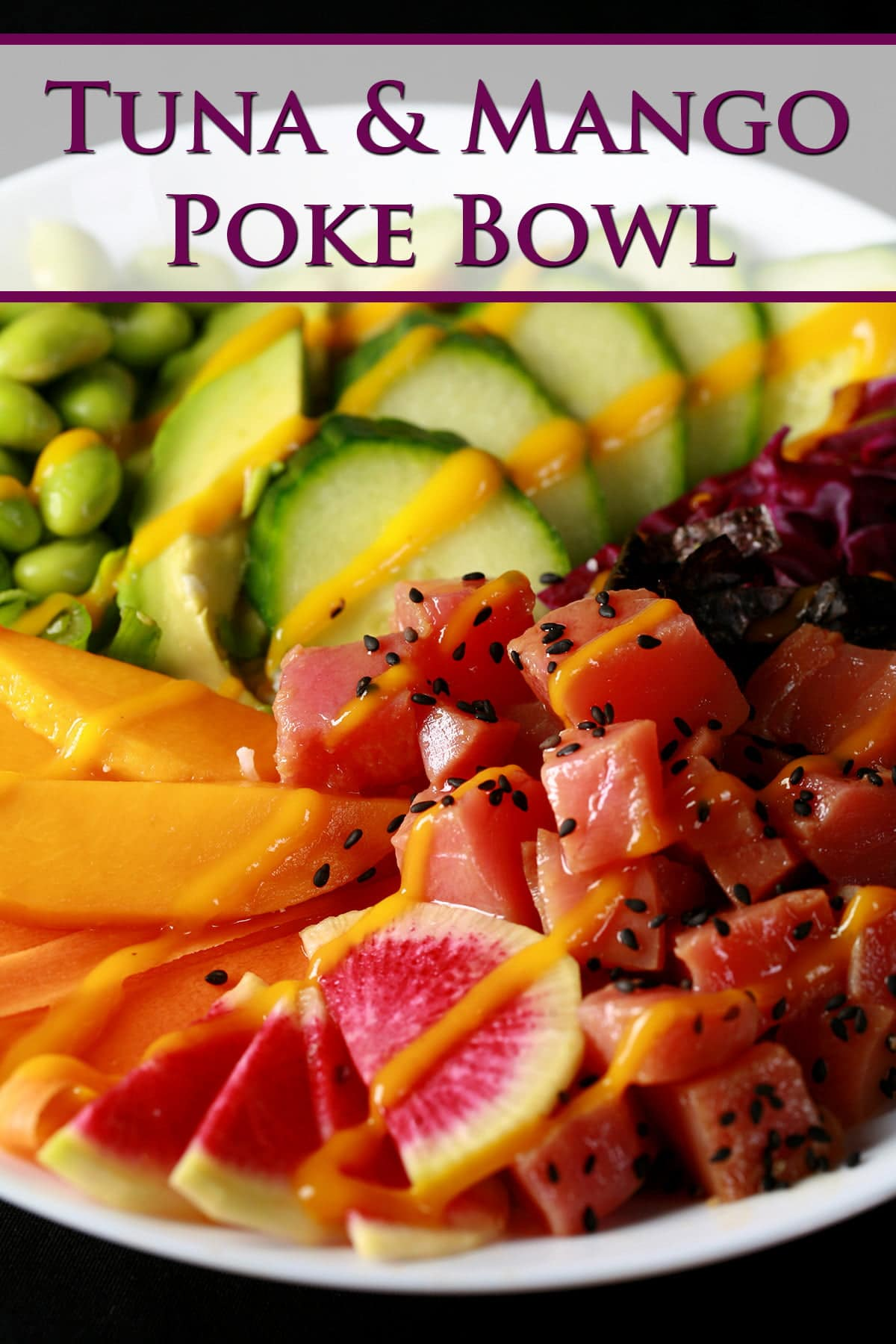 Close up view of a colourful bowl of tuna mango poke. There is a rainbow of vegetables and fruit, including purple cabbage, watermelon radish, carrots, mango, edamame, avocado, and cucumber.