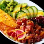 Close up view of a colourful bowl of tuna mango poke. There are a rainbow of vegetables and fruit, including purple cabbage, watermelon radish, carrots, mango, edamame, avocado, and cucumber