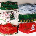 "An array of 6 gaudily decorated ""Ugly Christmas Sweater"" style face masks, on a white background."