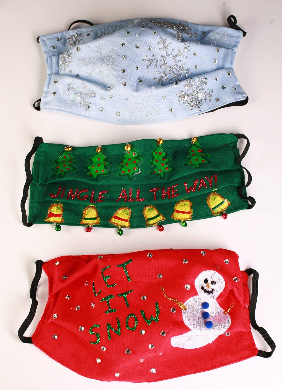 "An array of 3 gaudily decorated ""Ugly Christmas Sweater"" style face masks, on a white background."