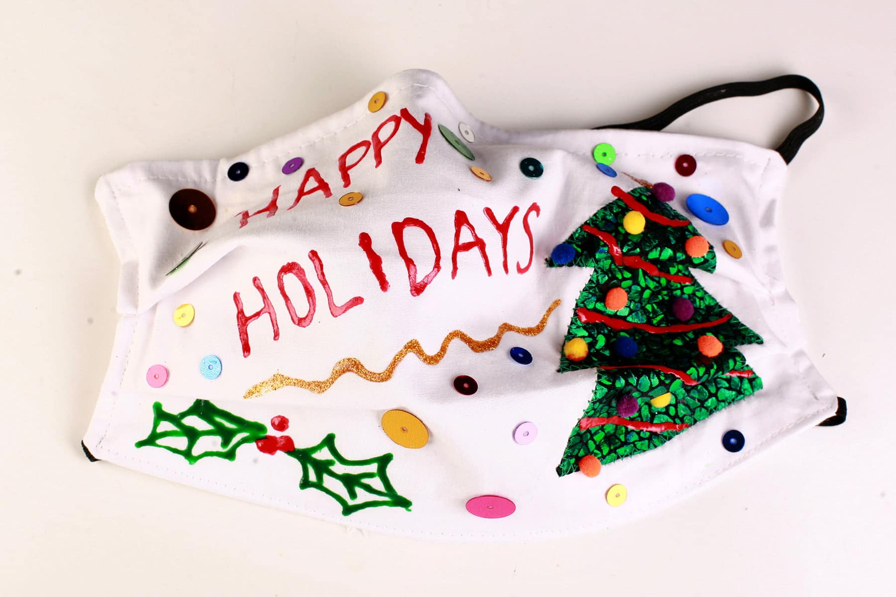"A white ""Ugly Christmas Sweater"" style face mask. It says ""Happy Holidays"" in red, with a green christmas tree and sequins all over it."