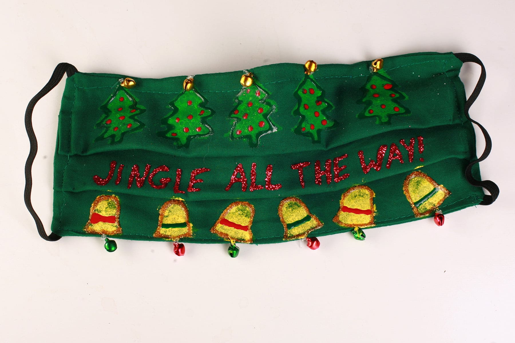 "A green mask with ""Jingle all the way"" written across it in red.  There is a line of green christmas trees across the top, and a line of yellow bells across the bottom."