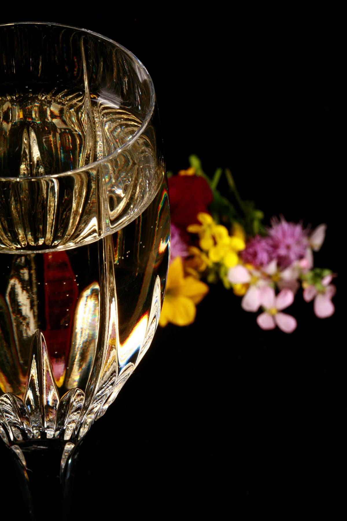 A close up photo of a glass of mead, with random wildflowers at the base of the glass.