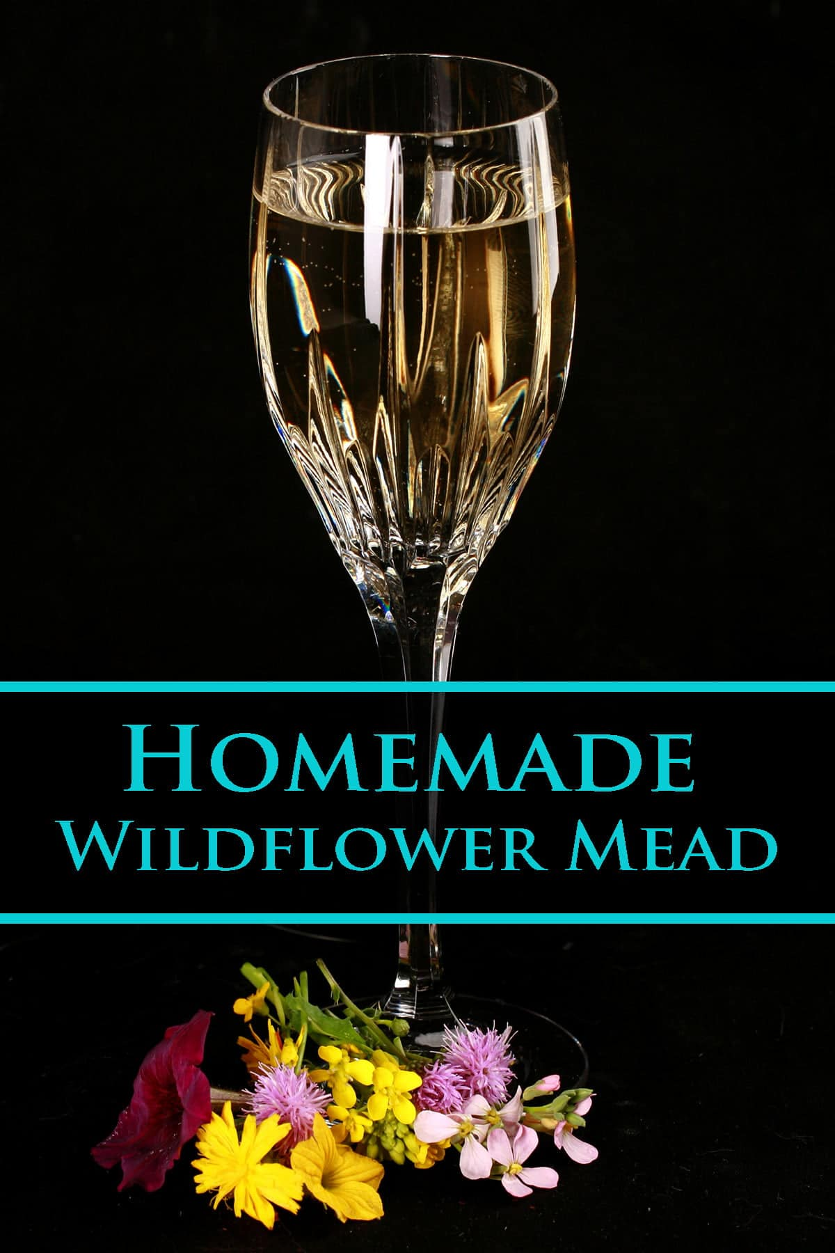 Glass of homemade wildflower mead in a tall wine glass. There are flowers at the base of the glass.