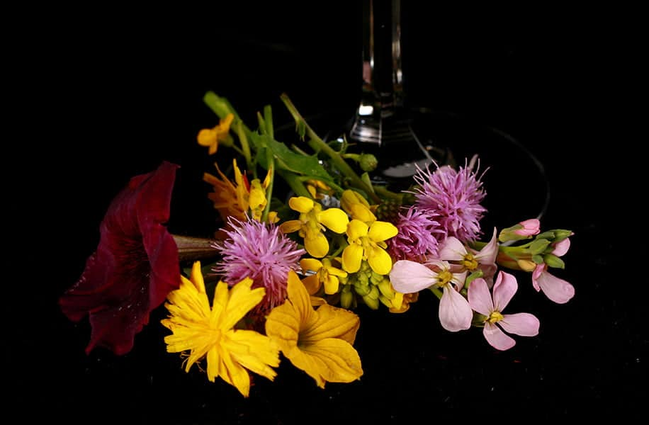 Flowers at the base of a wine glass, against a black background.