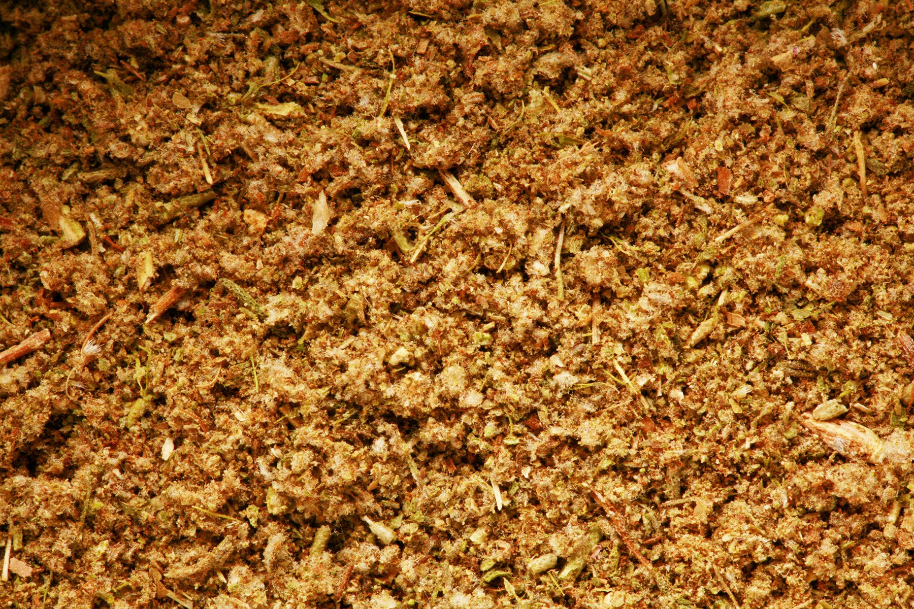 A close up view of AIP compliant poultry seasoning. A fluffy looking brownish green herb mix.