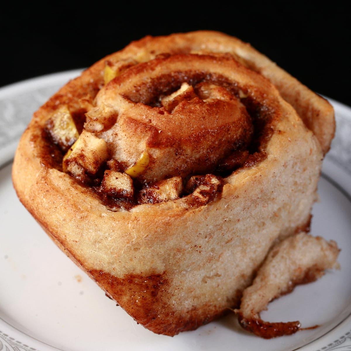 Close up photo of an apple cinnamon bun - a cinnamon bun, with small pieces of apple throughout the cinnamon swirl.