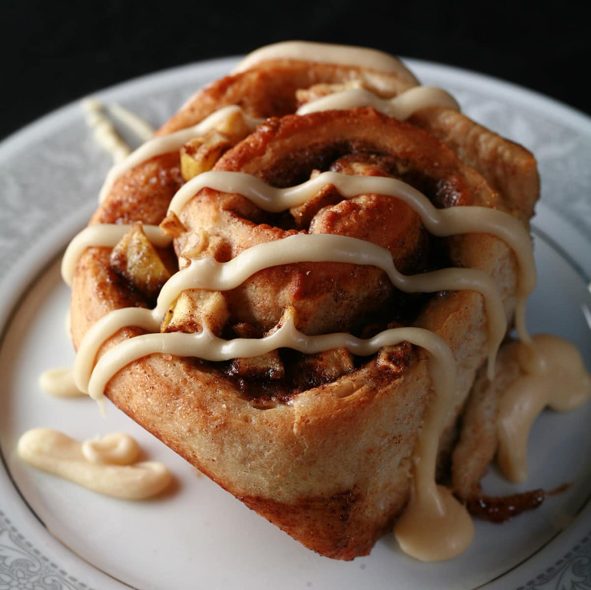 Close up photo of an apple cinnamon bun - a cinnamon bun, with small pieces of apple throughout the cinnamon swirl - drizzled with maple glaze.