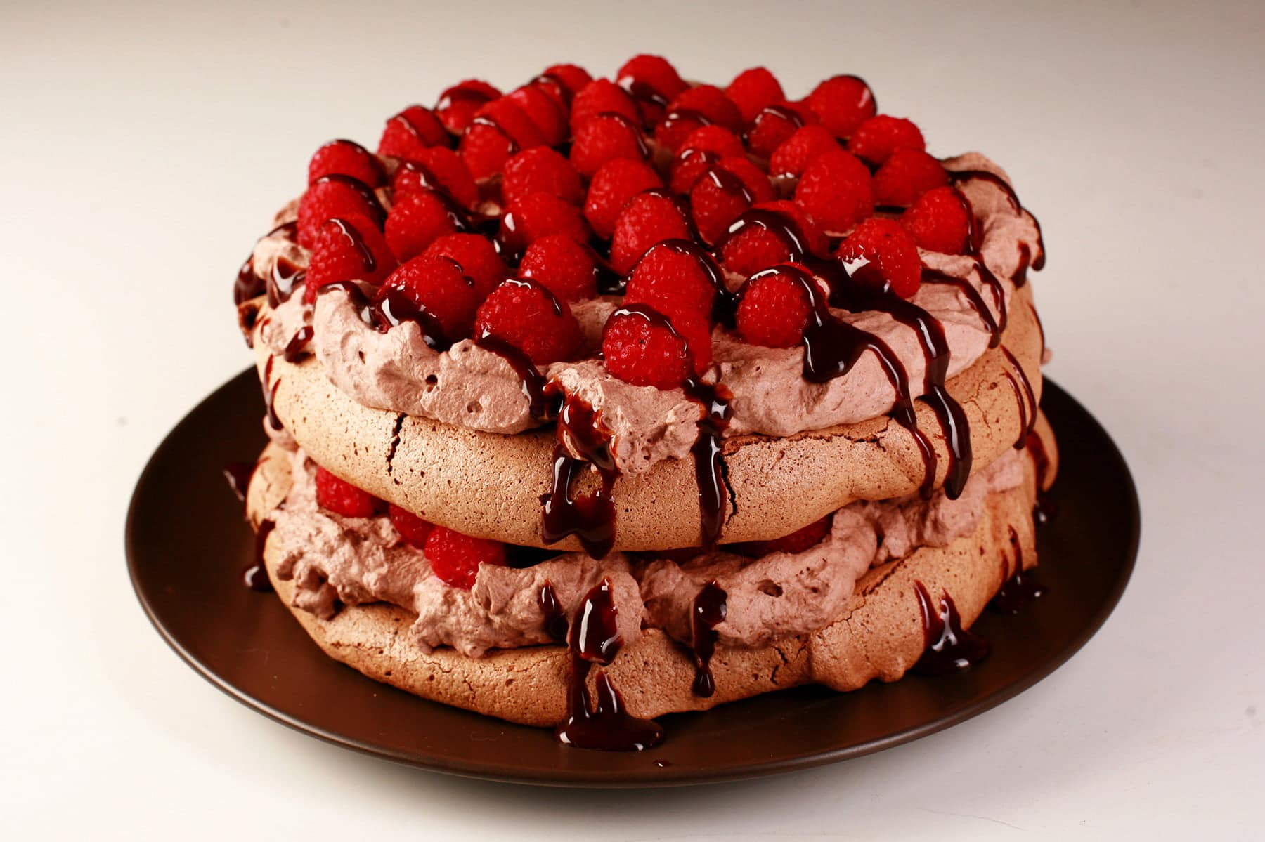 A double layered chocolate pavlova on a brown plate. Two layers of chocolate meringue are sandwiches with layers of chocolate whipped cream and raspberries, drizzled with chocolate sauce.