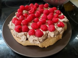 A large round chocolate meringue on a brown plate, topped with chocolate whipped cream and raspberries.