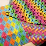 A stack of folded lengths of brightly coloured print fabric.