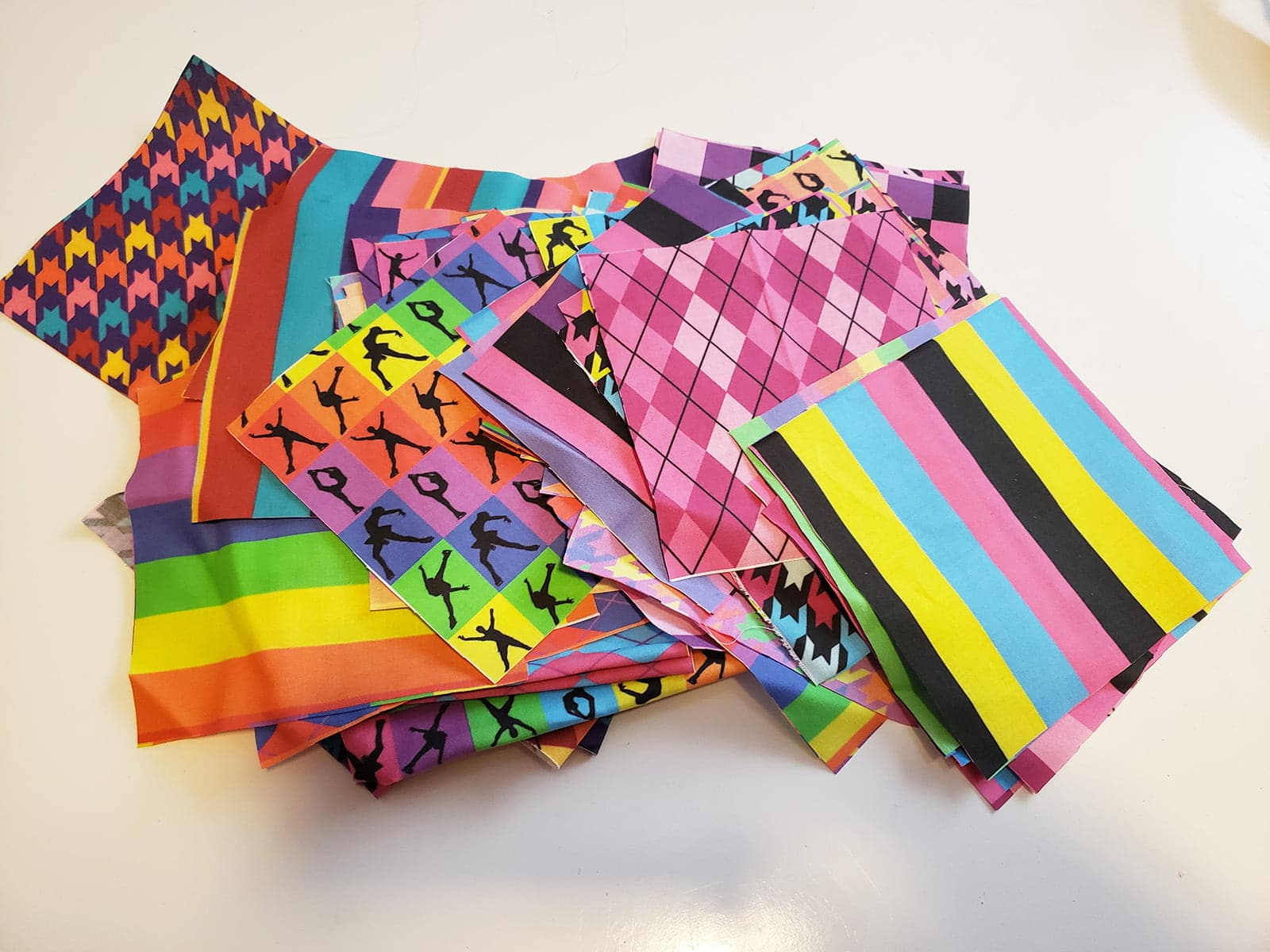 A stack of small squares of brightly coloured print fabric.