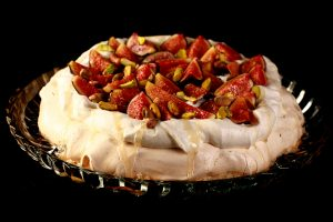 An ivory coloured meringue round, piled with whipped cream, sliced figs, and pistachios. A drizzle of honey finishes it off.