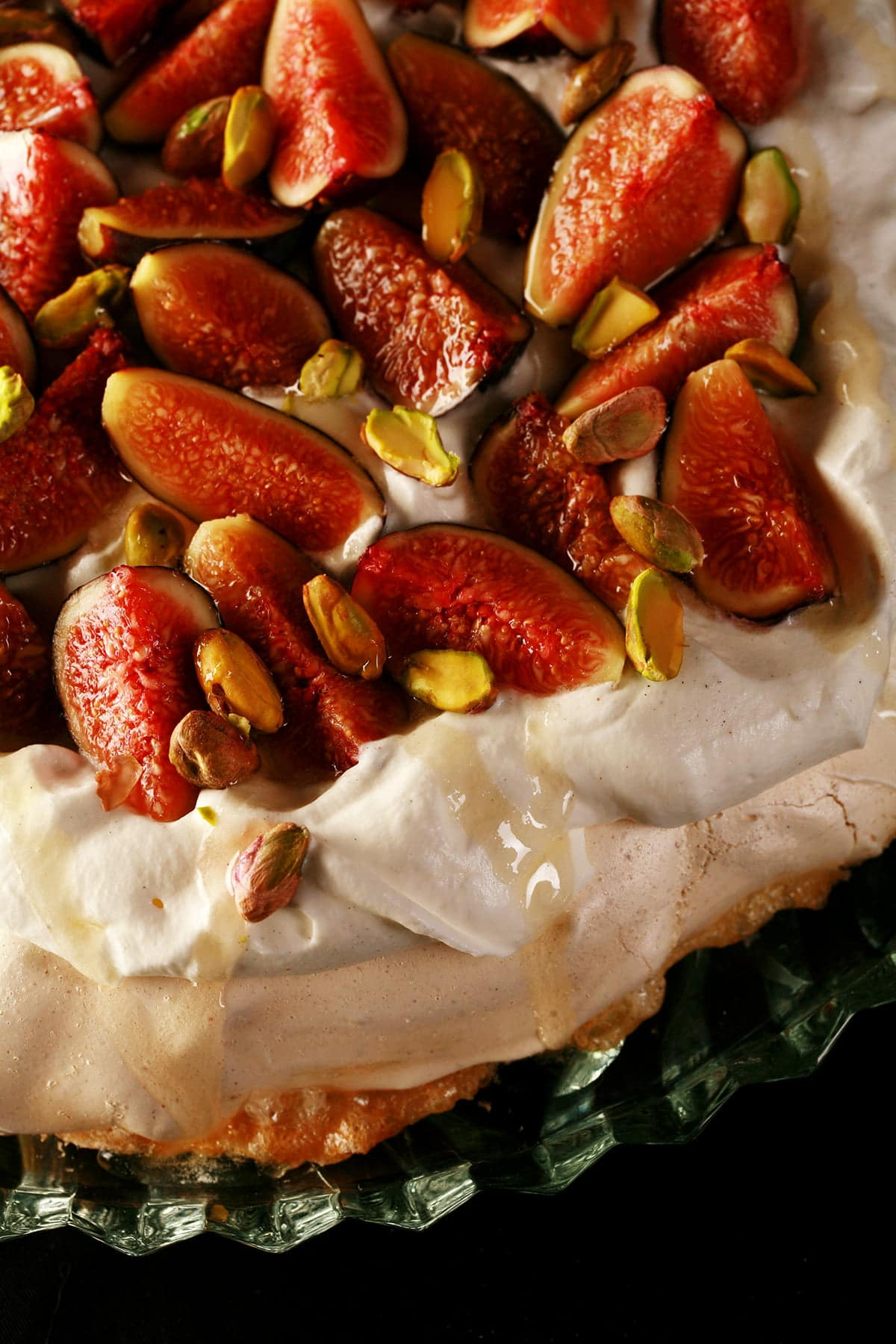 An ivory coloured Pavlova meringue round, piled with whipped cream, sliced figs, and pistachios. A drizzle of honey finishes it off.
