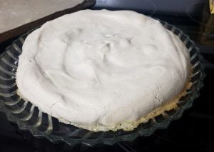 A baked Pavlova base - an ivory coloured baked meringue, on a glass serving dish.