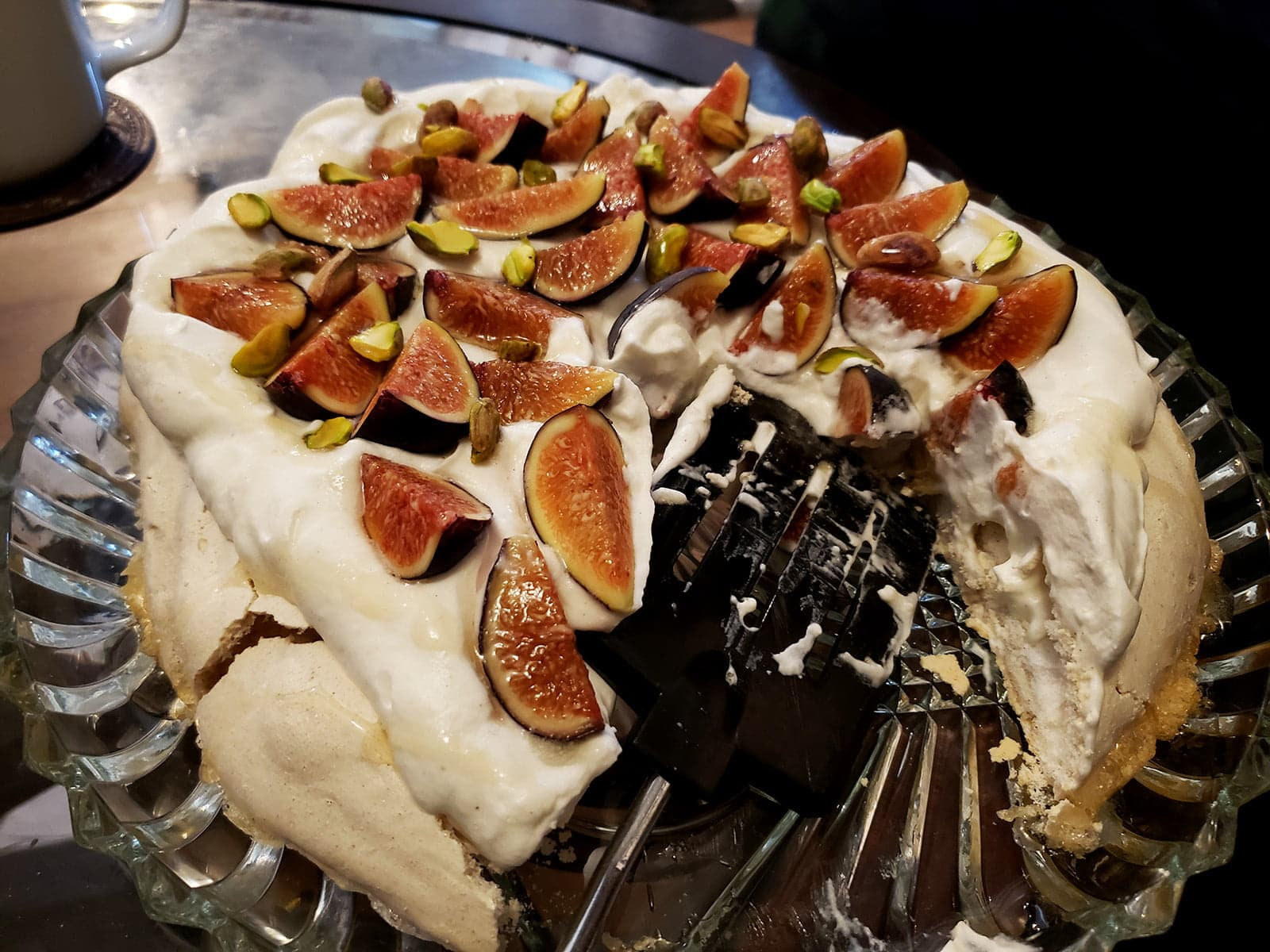 An ivory coloured Pavlova meringue round, piled with whipped cream, sliced figs, and pistachios. It's half eaten, on a glass serving plate.  A Cardamom fig pavlova.