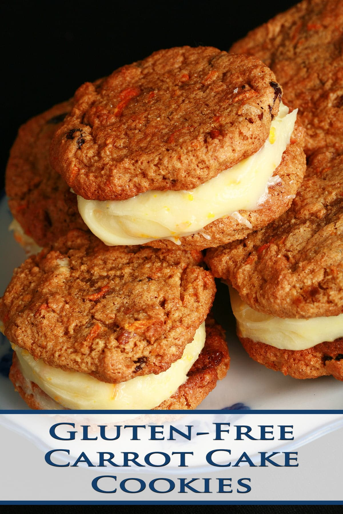 A small blue and white plate with a stack of gluten-free carrot cake sandwich cookies on it. The filling is ivory coloured and has flecks of orange zest throughout.