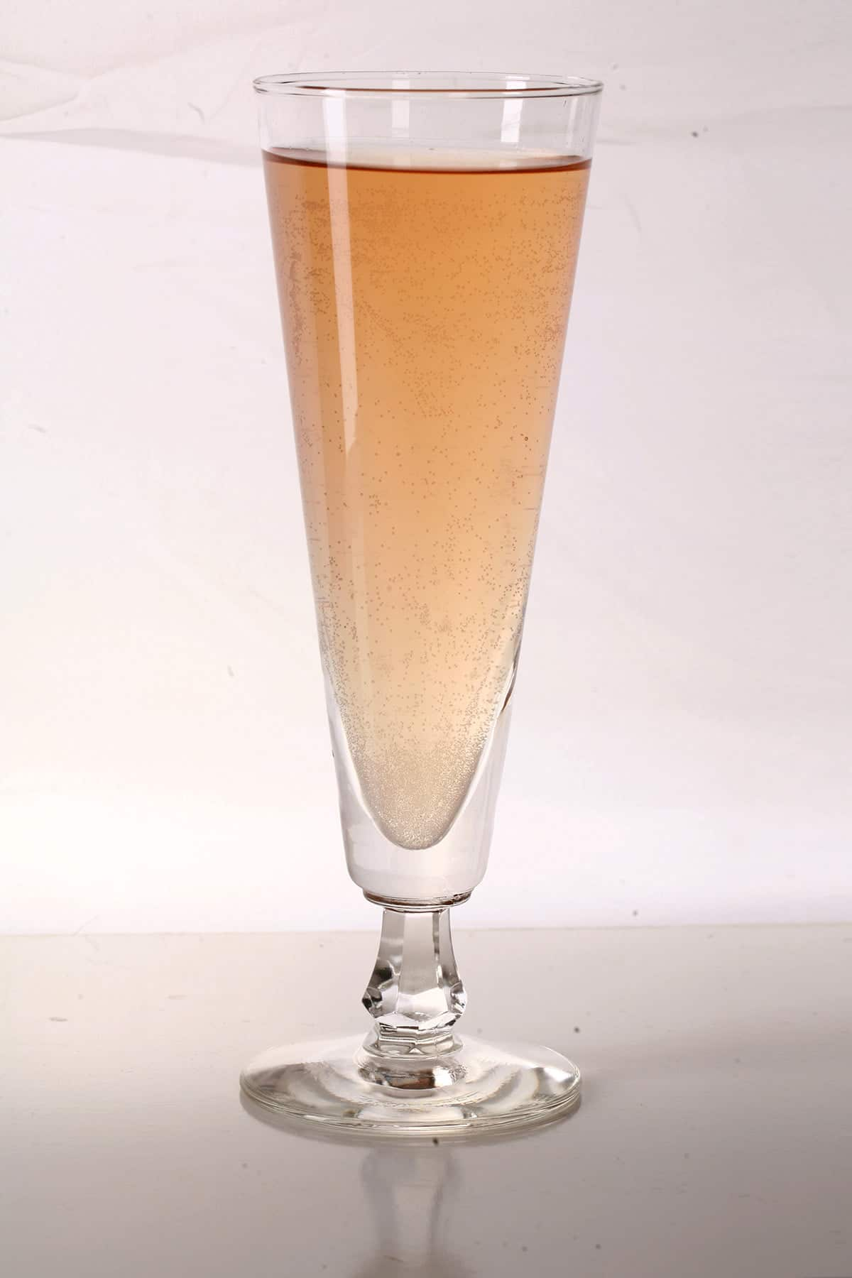 A beer flute filled with hard iced tea, against a white and greyish background.
