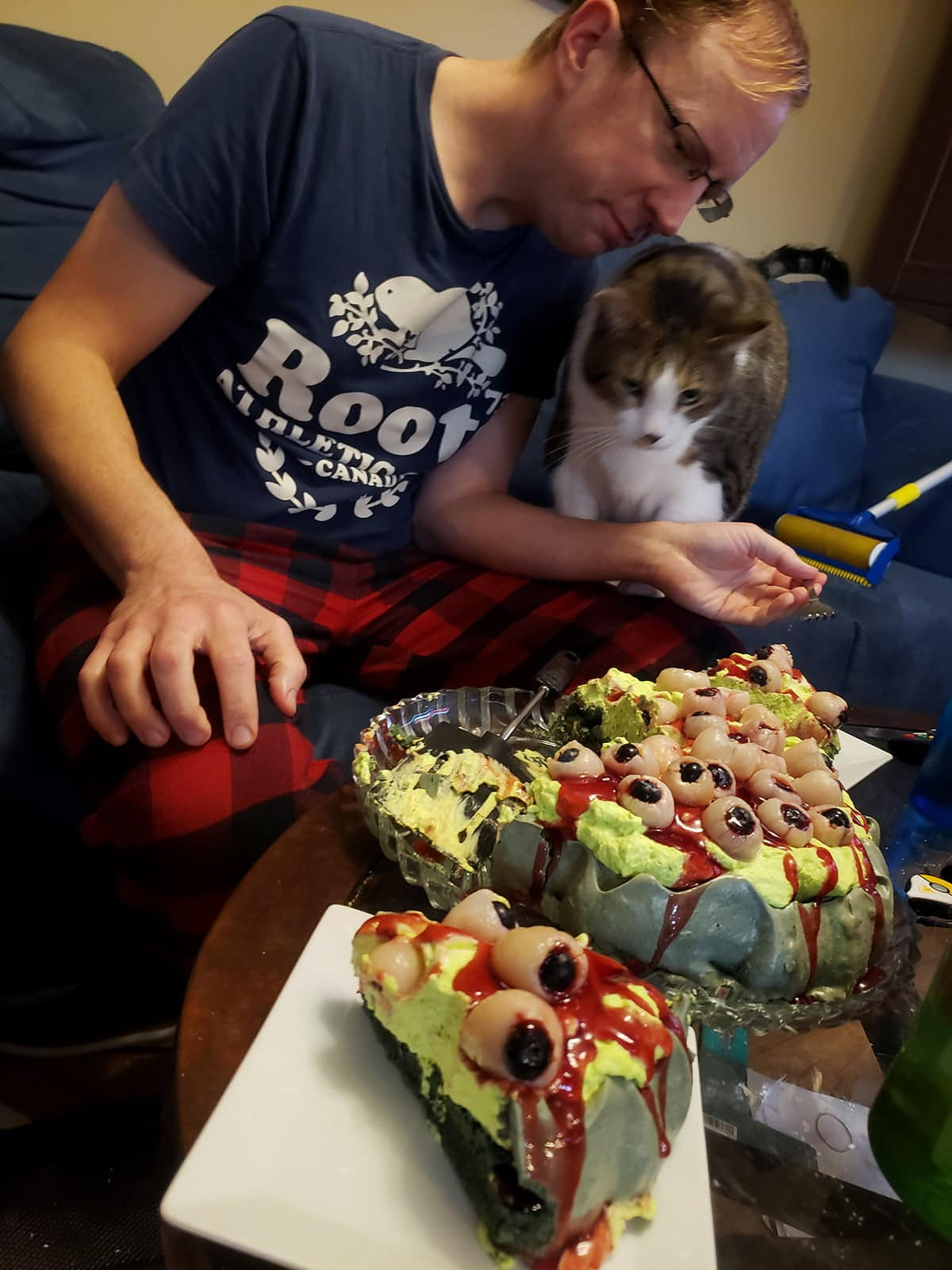 A grown man in a Roots shirt and plaid PJ bottoms valiantly defends his slice of pavlova from a 32 lb cat.