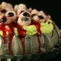 """A close up view of a Halloween Pavlova - dark grey meringue base, bright green whipped creamm """"bloody eyeballs"""" made from lychees, raspberry jam, and blueberries, and oozing raspberry-honey """"blood""""."""