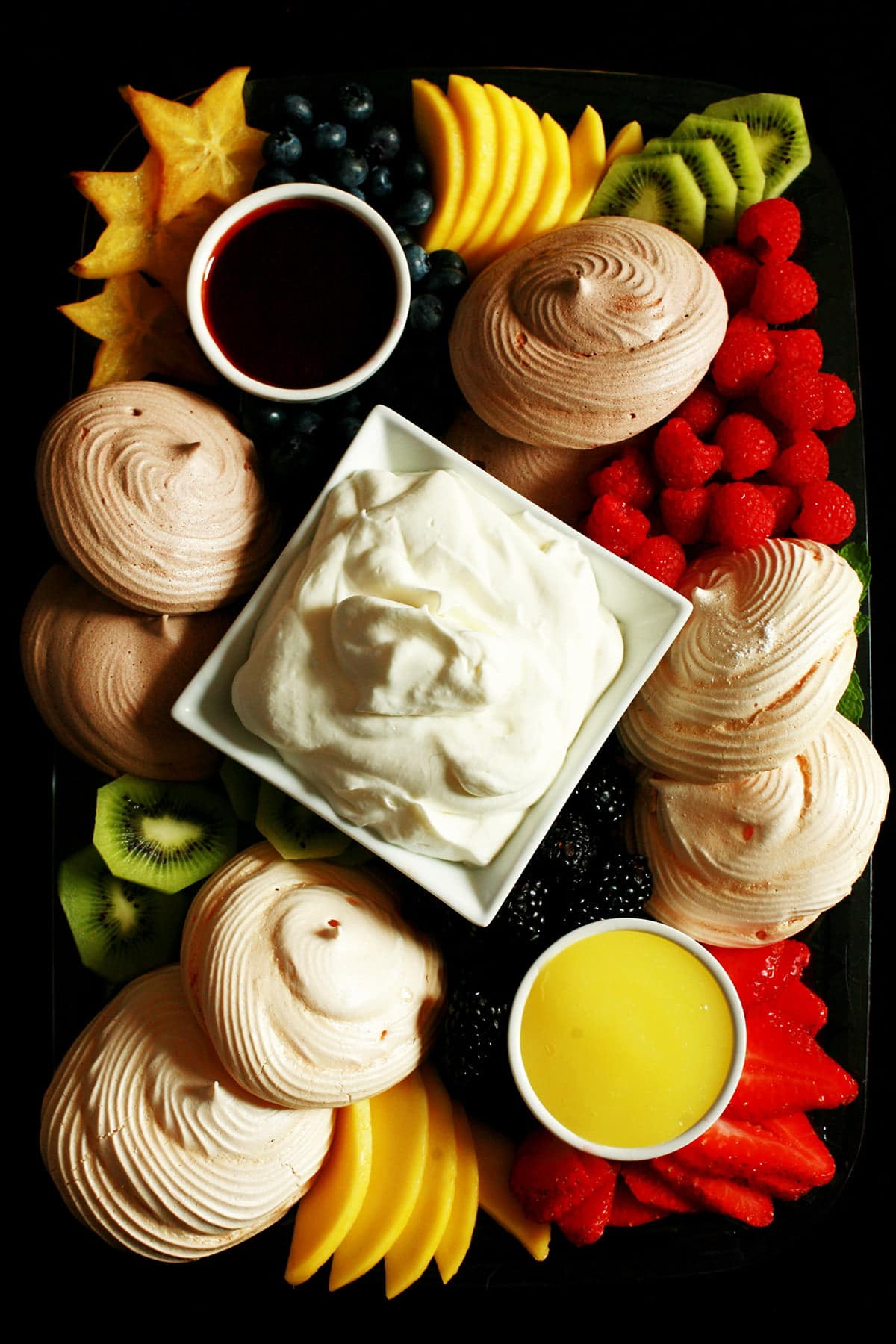 A Pavlova Dessert Charcuterie board: A bowl of whipped cream and two little bowls of sauce - lemon curd and chocolate sauce - are surrounded by mini pavlova meringues and a selection of fresh fruits.