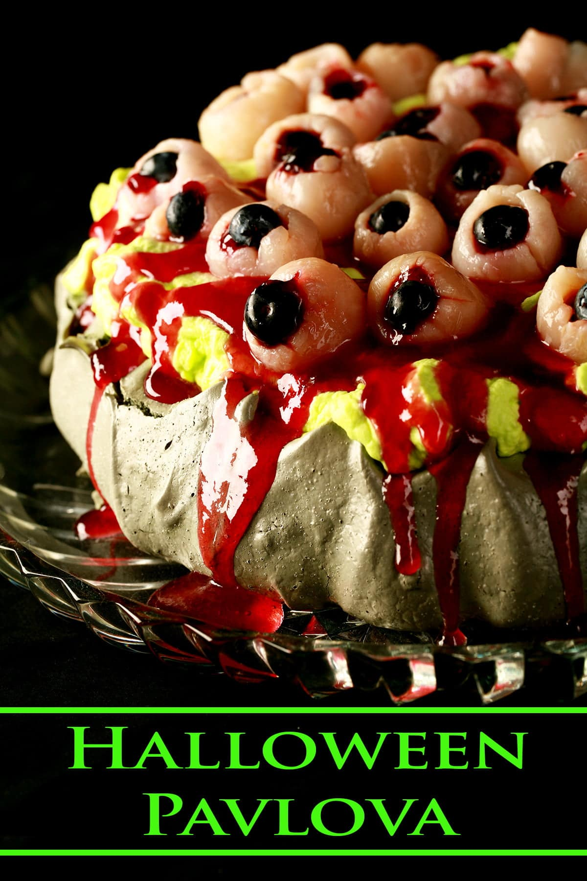 "A close up view of a Halloween Pavlova - dark grey meringue base, bright green whipped creamm ""bloody eyeballs"" made from lychees, raspberry jam, and blueberries, and oozing raspberry-honey ""blood""."