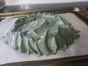 A round of dark grey meringue on a parchment lined baking sheet.