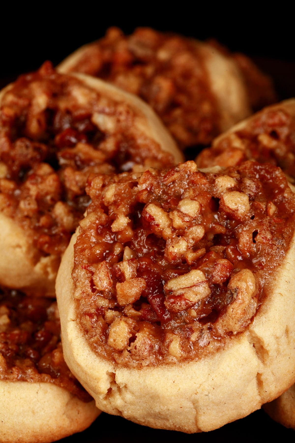 A small plate with Pecan Pie Cookies on it. Each cookie is round and golden brown, with a center indentation filled with chopped pecans and caramelized brown sugar.