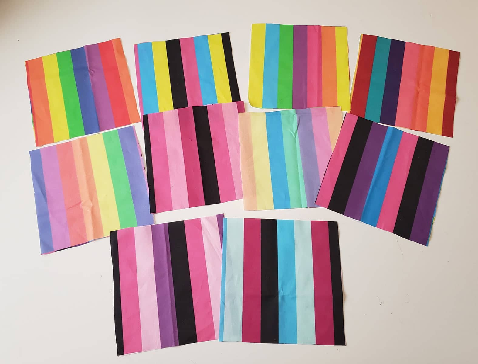 Several square cuts of brightly coloured print fabric are arranged against a white background.