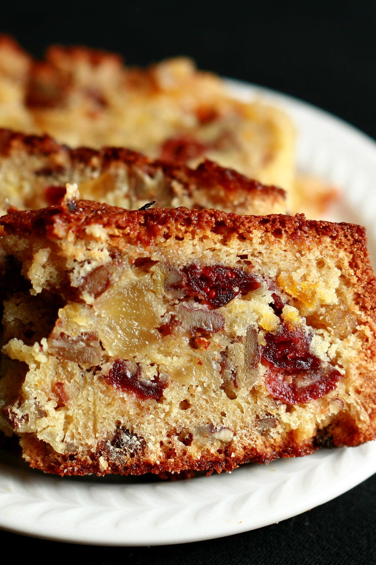 Slices of fruitcake, on a small white plate. The cake is generously studded with dried - not candied - fruit.